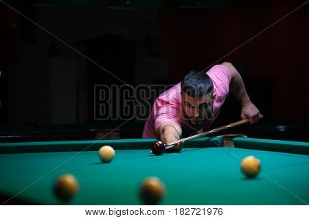 Young concentrated man aiming to take the snooker shot. Male adult playing billiard game.