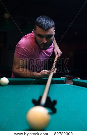 Young caucasian man playing billiard game. Male adult wearing casual cloth aiming to take the snooker shot.
