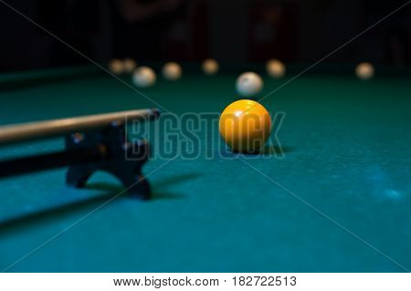 Billiard cue is aiming to take the snooker shot. Green table with balls on background