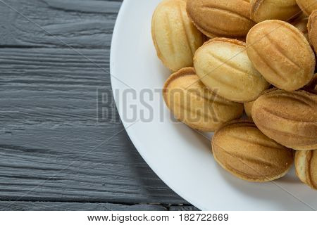 Pile of cookies with condenced milk on white plate, wooden background