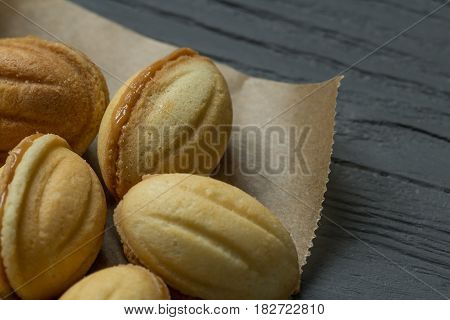 Cookies with boiled condenced milk on cooking paper, close-up