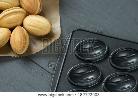 Cookies with condenced milk and baking-mold on wooden background