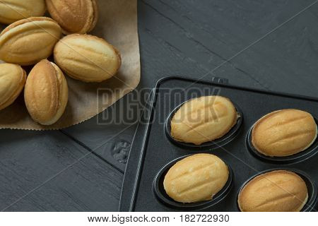 Cookies with condenced milk and filled baking-mold on wooden background