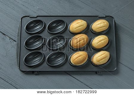 Baking-mold filled in a half of cookies, wooden background