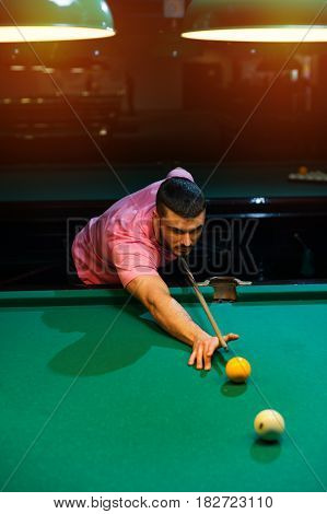 Young caucasian man playing billiard in club. Male adult aiming the ball.