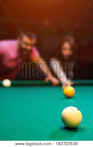 Young romantic couple aving fun hplaying billiard game in dark club. Young brunette girl aiming to take a snooker shot, while man standing next to her and looking at table. Defocused background.