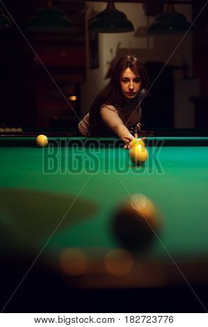 Playing billiard background - young brunette girl aiming to take the snooker shot.