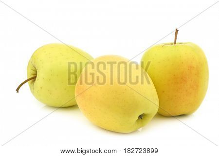 three fresh yellow apples and a cut one on a white background