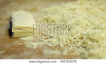 Noodles Roll On The Cutting Board Near Of Heap Of Noodles