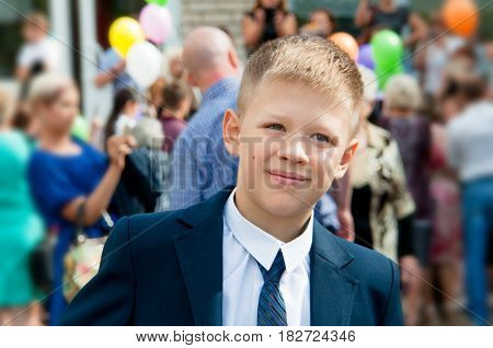The boy in a suit near the school