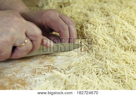 Cutting Of Noodles Roll On Cutting Board By Hands Close Up