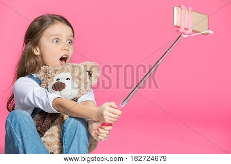 Shocked Little Girl With Teddy Bear Taking Selfie On Pink