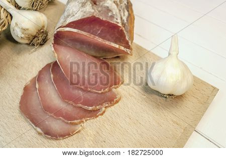 Cutting smoked sirloin with garlic on a table