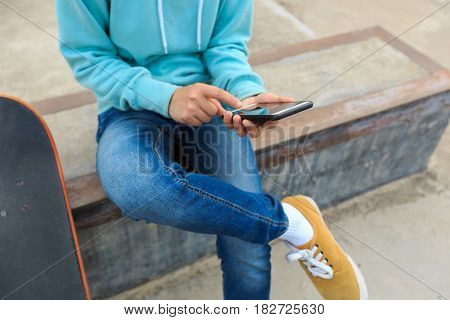 closeup of skateboarder use cellphone at skatepark