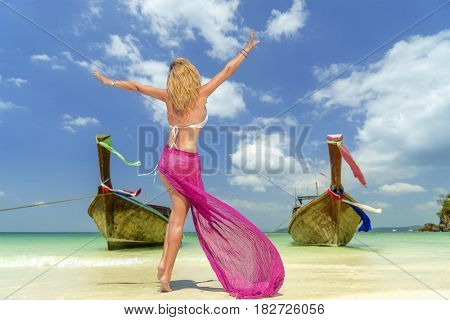Woman on Tropical beach relaxing and watching longtail boats, Andaman Sea, Thailand