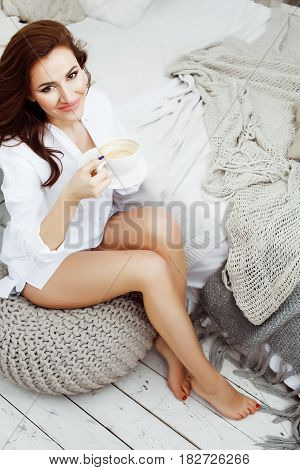 young pretty brunette woman in her bedroom sitting at window, happy smiling lifestyle people concept close up