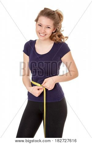 Attractive woman in sports wear holding measuring tape. All on white background.