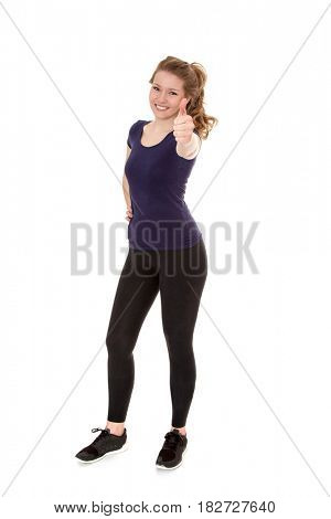 Full length shot of an attractive woman in sports wear showing thumbs up. All on white background.