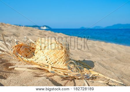Straw hat lying on the tropical beach against the background of sea. Carefree bliss freedom travel and relax concept.