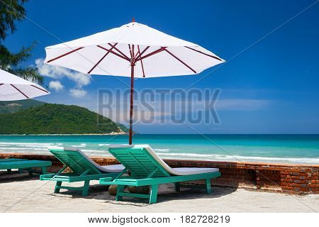 Two deck chairs under a white umbrella on tropical beach. Travel background.