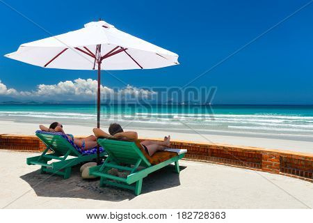 Happy couple leisure on a tropical beach on deck chairs under a white umbrella.