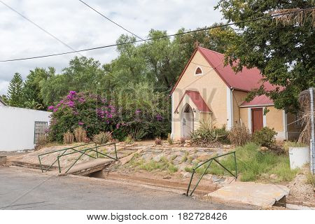 CALITZDORP SOUTH AFRICA - MARCH 24 2017: The St. Marks Chapel of the Anglican Church in Calitzdorp was built in 1880. An irrigation canal is visible next to the street.