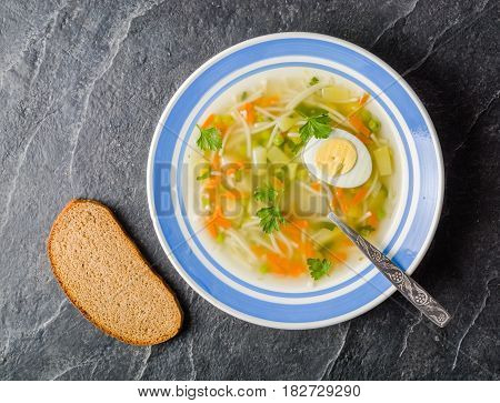 Soup With Egg, Pasta And Vegetables In A Blue Plate On A Black Background.