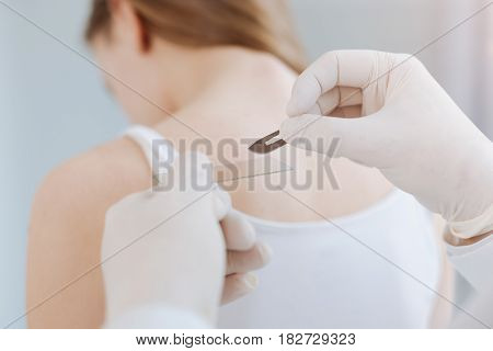 Checkup of all skin. Concerned skilled proficient dermatologist working in the clinic and using professional instruments while patient sitting in the cabinet