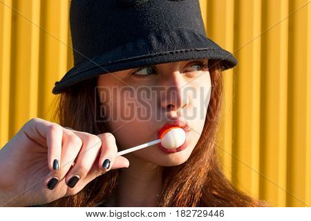 Cheerful Stylish Young Girl In Hat, And Jeans Jacket With Candy On Stick, Chupa Chups, On Sunny Day