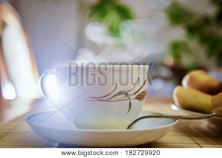 Steam rises over the white teacup with hot tea on the table in the room