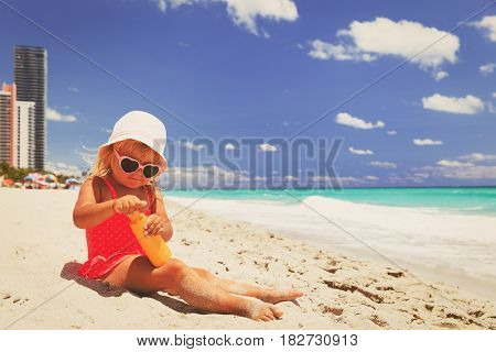 sun protection -cute little girl with sunblock cream on beach
