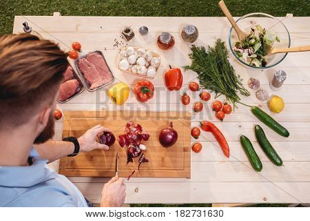 Top View Of Man Cutting Fresh Onion At Wooden Cutting Board For Barbecue