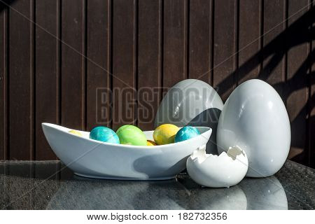 Set of colorful shiny Easter eggs and grey and white colored ceramic