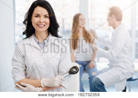With individual attitude to every patient. Smiling charming beautiful dermatologist working in the clinic and holding dermatoscope while colleague talking to young patient in the background poster