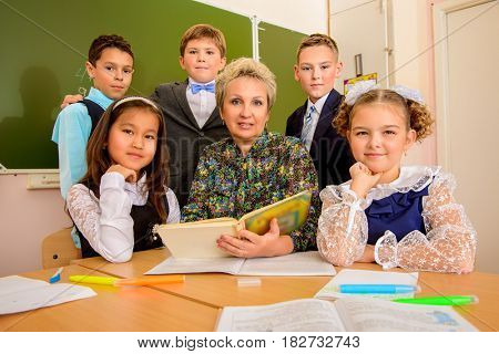 Favorite teacher. Portrait of students with their teacher during the lesson. Educational concept.