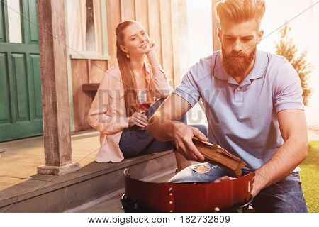 Smiling Young Woman Drinking Wine And Looking At Man Kneeling Near Outdoor Grill