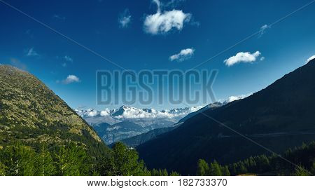 Snow capped mountains under deep blue sky. View from the valley through the forest and trees