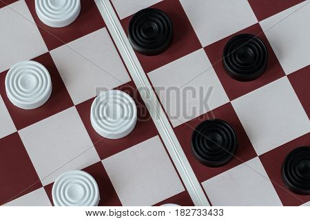 White and black checkers on gaming board, close-up