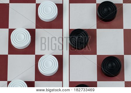Black and white checkers on gaming board, top view