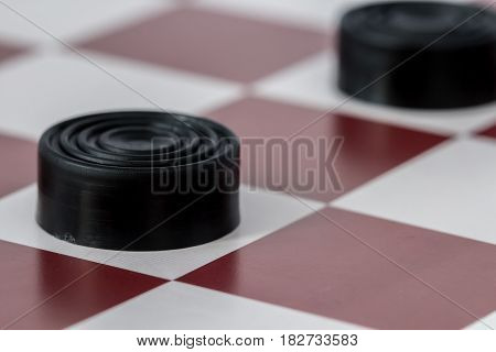 Black checkers close-up on gaming board, macro