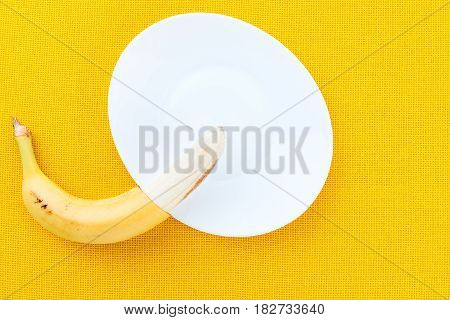 Half-cleaved Yellow Ripe Bananas From The Tropics On A White Plate And Yellow Fabric Background With