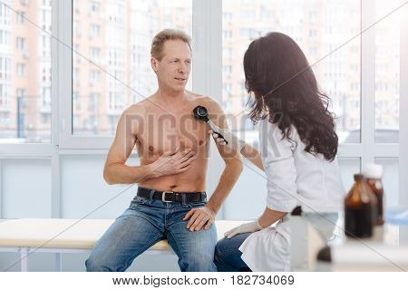 Using modern technologies for skin examination. Attentive diligent optimistic dermatologist working in the clinic and having conversation with man while examining patient skin with dermatoscope