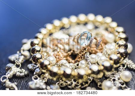 Gold ring with a large blue topaz and a shiny gold bracelet on a bright pearl necklace on a dark background. Luxury jewelry concept.