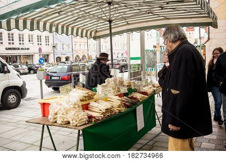Neuoetting,Germany-April 19,2017: A man looks at asparagus for sale in a local farmers' market