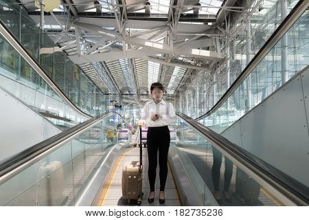 Asian young businesswoman with luggage down the escalator in airport. business travel.