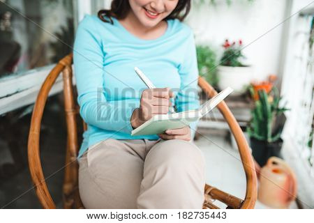 Beautiful asian woman at home writing and working with diary