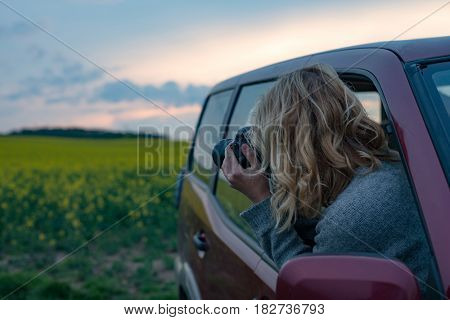 Photographer woman taking picture on road trip at sunset. Making travel blog.
