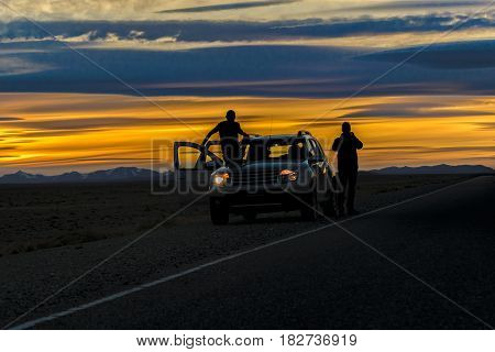 Patagonian sunset landscape scene with two men with van parked in the middle of route Santa Cruz Province Argentina
