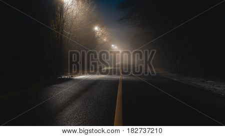 abstract fogy road with lanterns at night