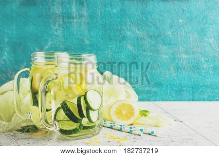 Fresh Summer Drink. Healthy detox drink with cucumber lemon and celery in glass jars on a light background